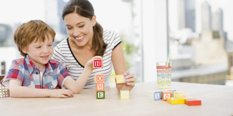 Mother watching son stacking alphabet blocks and spelling home